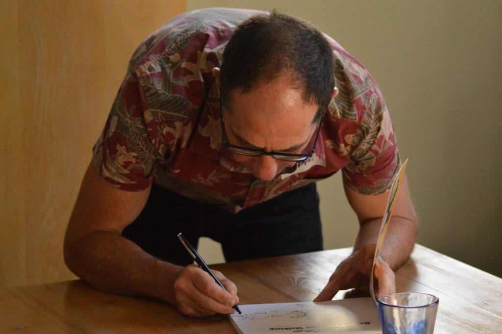 Jonathan Shapiro signing one of the books beneath Rosemary's signature.